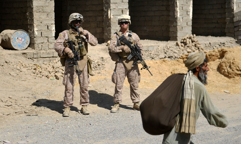 <p>An elderly Afghan walks past US Marines from Kilo Company of the 3rd Battalion 8th Marines Regiment while they conduct a patrol in Garmser, Helmand Province on June 29, 2012.</p>