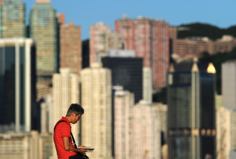 <p>A woman reads a book before residential and commercial buildings in Hong Kong on July 3, 2012.</p>