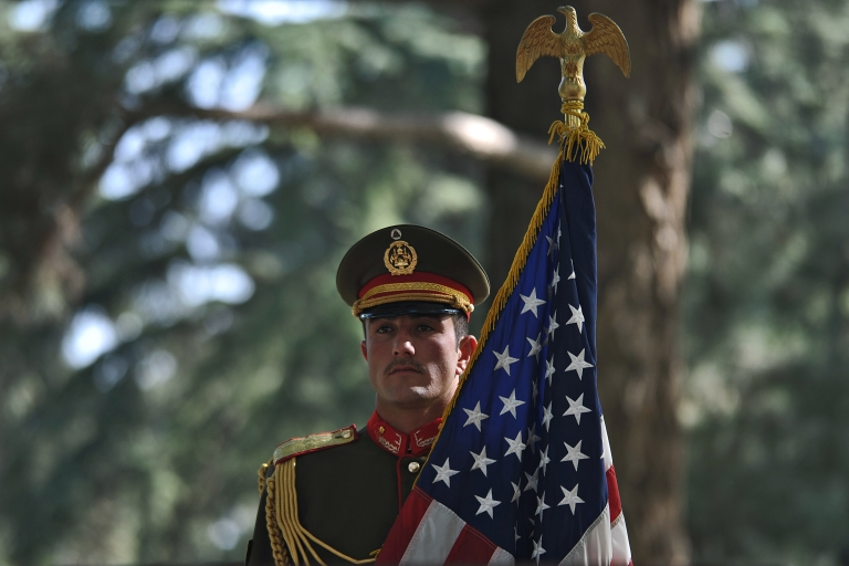 <p>An Afghan military serviceman holds the US flag during a press conference attended by Afghan President Hamid Karzai and US Secretary of State Hillary Clinton at the Presidential Palace in Kabul on July 7, 2012.</p>