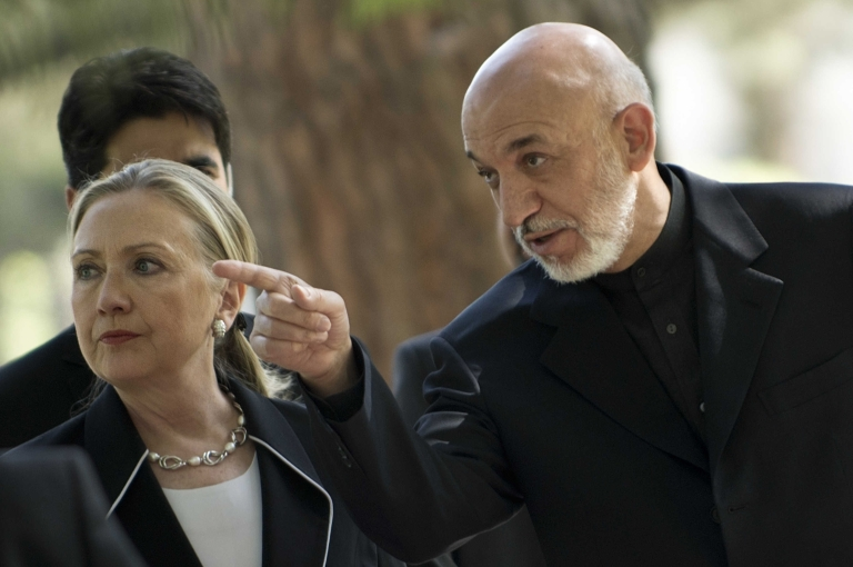 <p>US Secretary of State Hillary Clinton walks with President of Afghanistan Hamid Karzai to a press conference at the Presidential Palace in Kabul on July 7, 2012.</p>