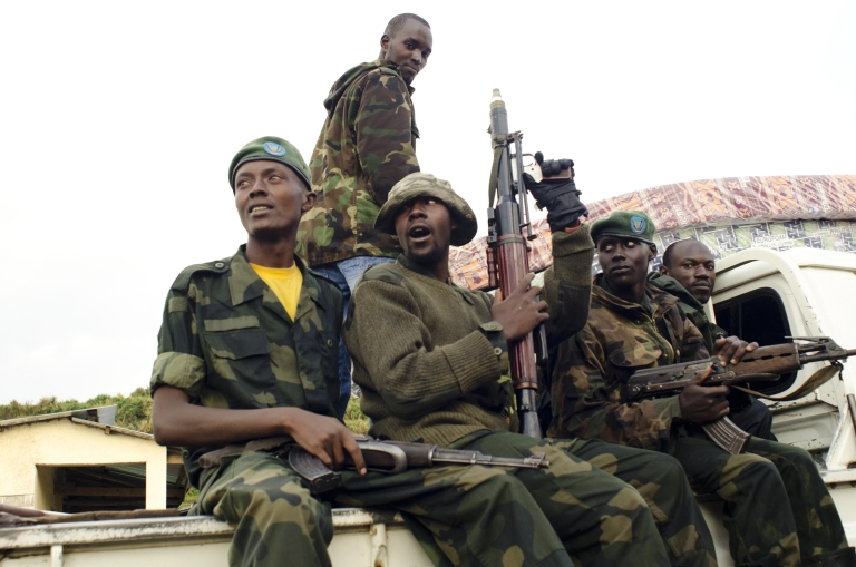 <p>M23 rebels sit at the back of a pick-up truck captured a week before and formerly used by the Armed Forces of the Democratic Republic of Congo, as they carry supplies through Bunagana, on July 15, 2012.</p>