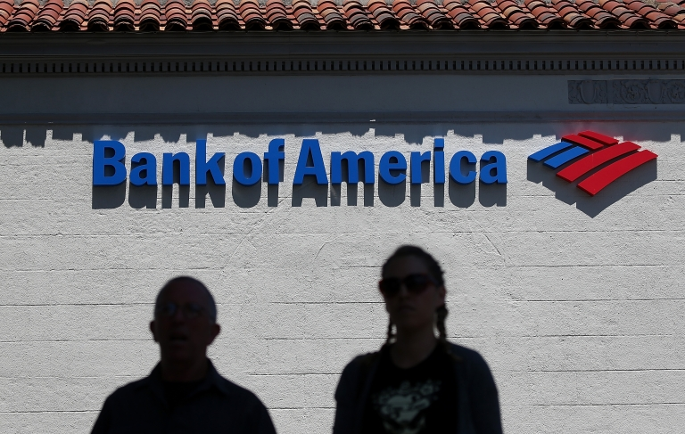 <p>People walk by a Bank of America branch office on July 18, 2012 in San Anselmo, California.</p>