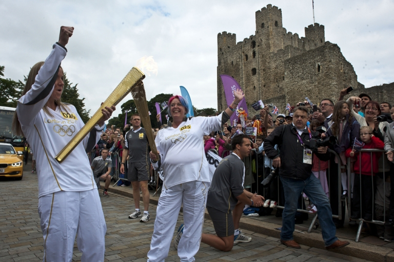 <p>Torchbearer Jessica Cheesman passes the Olympic flame to Sarah Mooney outside of Rochester Castle during Day 63 of the London 2012 Olympic Torch Relay on July 20, 2012 in Rochester, England. The Olympic flame is now on day 63 of a 70-day relay involving 8,000 torchbearers covering 8,000 miles.</p>