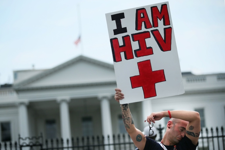 <p>HIV+ patient Aaron Laxton of St. Louis, Missouri, holds up a sign in front of the White House after a march from the Washington Convention Center July 24, 2012 in Washington, DC. AIDS activists from organizations all around the world participated in the march to 'demand rights and resources to confront and cure HIV/AIDS.</p>