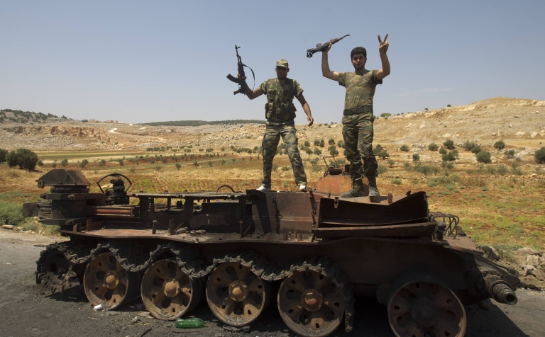 <p>Syrian rebel fighters pose on a destroyed army tank in the northern town of Atareb, 15 miles east of Syria's second largest city Aleppo, on July 31, 2012.</p>
