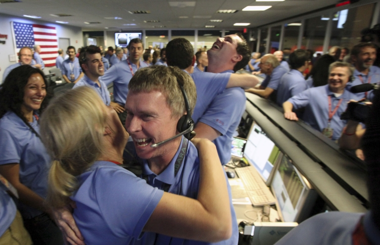 <p>Telecom engineer Peter Ilott hugs a colleague, celebrating a successful landing inside the Spaceflight Operations Facility for NASA's Mars Science Laboratory Curiosity rover at Jet Propulsion Laboratory on August 5, 2012 in Pasadena, California.</p>