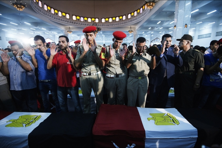 <p>Relatives and friends pray over the coffins of soldiers killed during a border post attack in Northern Sinai, during their funeral on August 7, 2012 in Cairo, Egypt. Since then, President Mohamed Morsi has ordered security forces to take full control of the Sinai Peninsula. Yesterday, he dismissed key military officials and nullified a constitutional provision aimed at limiting presidential power.</p>