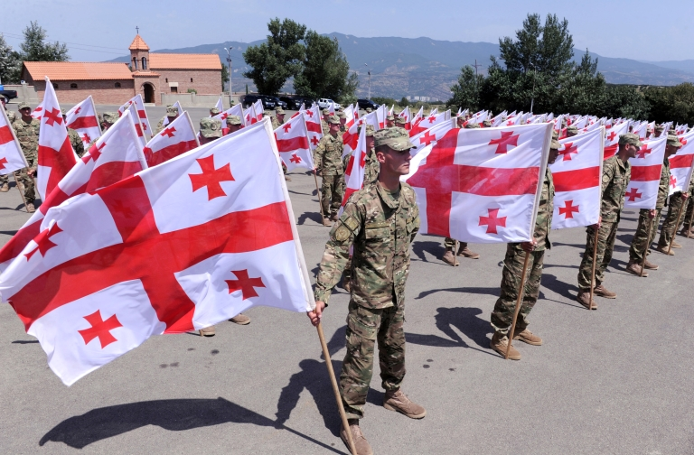 <p>Georgian soldiers hold national flags at a memorial cemetry in Tbilisi on August 8, 2012, as Georgians mark the anniversary of the Ossetian conflict.</p>