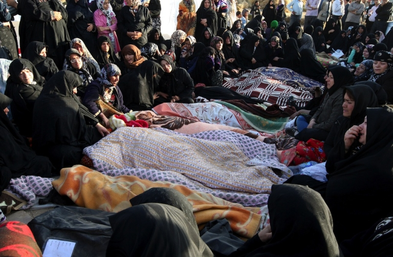 <p>Iranians mourn over the covered bodies of loved ones in the village Baje-Baj, near the town of Varzaqan, on August 12, 2012.</p>