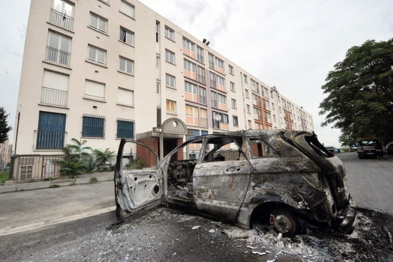 <p>A picture taken on August 14, 20102 shows a burnt car in Amiens, northern France. A riot in a deprived area of Amiens has left 16 police officers injured, a primary school severely damaged by fire and a sports centre completely destroyed.</p>