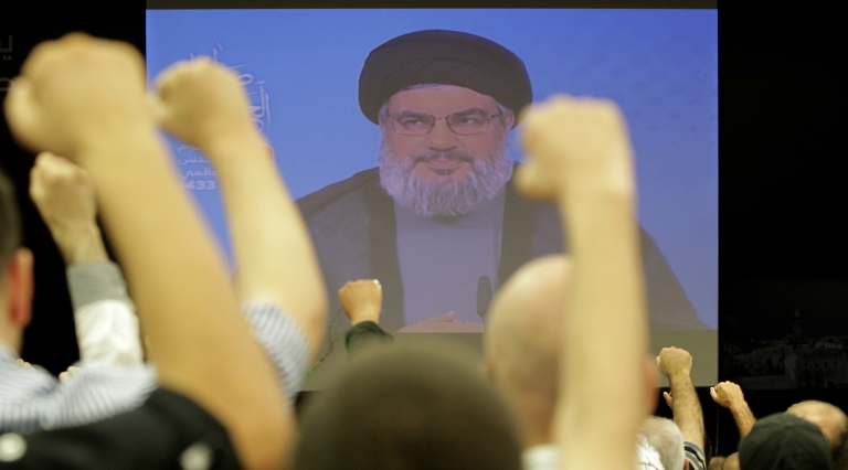 <p>Lebanese Shiite men raise their fists up as they listen to a speech via videolink by Hezbollah leader Hassan Nasrallah marking Al-Quds (Jerusalem) Day in the southern suburbs of Beirut on August 17, 2012 .</p>