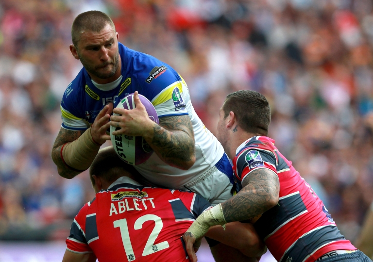<p>Paul Wood of Warrington Wolves offloads in the tackle from Carl Ablett of Leeds Rhinos during the Carnegie Challenge Cup Final between Leeds Rhinos and Warrington Wolves at Wembley Stadium on August 25, 2012 in London, England.</p>