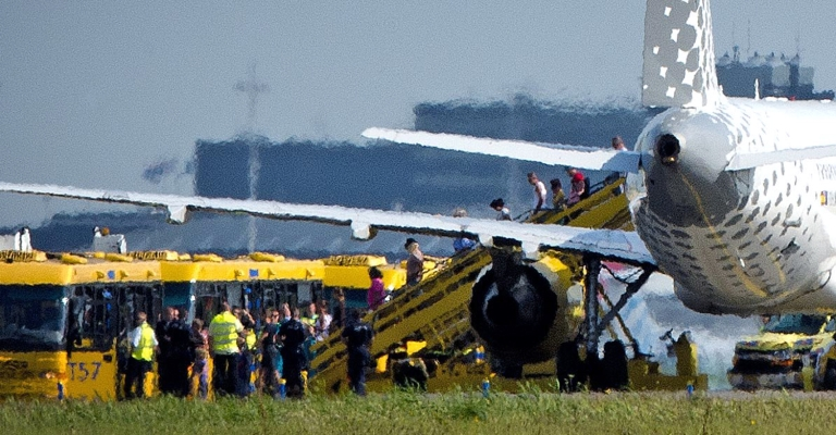 <p>Passengers disembark a plane of the Spanish company Vueling after it landed at Schiphol Airport in Amsterdam on August 29, 2012.</p>