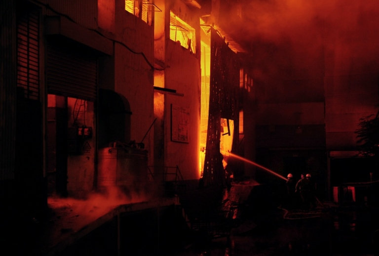 <p>Pakistani firefighters extinguish a fire that erupted in a garment factory in Karachi on September 11, 2012.</p>