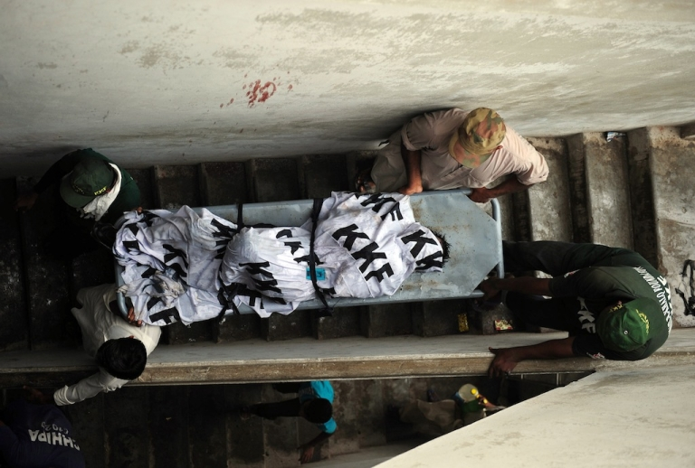 <p>Pakistani rescuers move the dead body of a garment factory worker.</p>