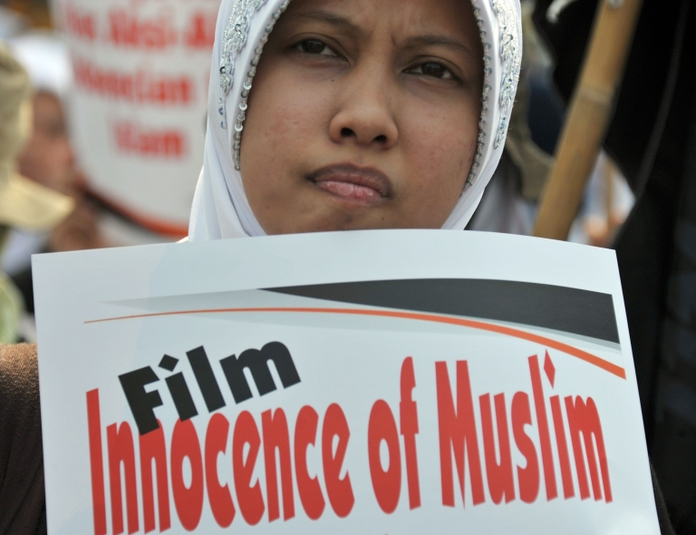 <p>A demonstrator holds a placard during a protest against the film 'Innocence of Muslims' in Jakarta, on September 14, 2012. More than 350 Muslim fundamentalists and their supporters staged an anti-US demonstration in Jakarta Friday, spewing anger at America over an anti-Islam film</p>