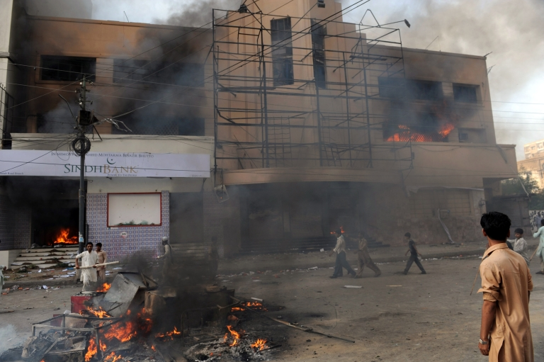 <p>Pakistani Muslim demonstrators are pictured in front of a burning cinema during a protest against an anti-Islam film in Karachi on September 21, 2012.</p>