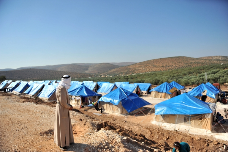 <p>A Syrian man looks at the tents of the new refugee camp at the village of Qah, northwestern Idlib, near the Turkish border, on October 14, 2012.</p>