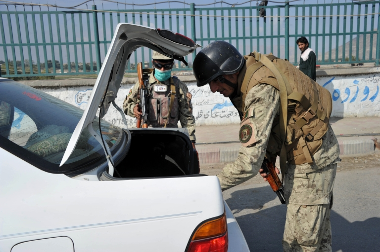 <p>Afghan security personel check passengers and cars at a checkpoint in the city of Jalalabad in Nangarhar province on October 20, 2012.</p>