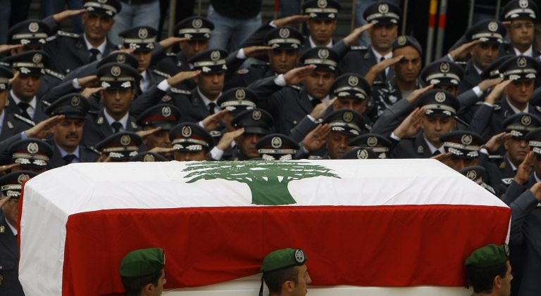 <p>Lebanese officers from the Internal Security Forces salute as the coffin of assassinated intelligence chief General Wissam al-Hassan passes Martyrs' square, Beirut, Oct. 21, 2012. (Stringer /AFP/Getty Images).</p>