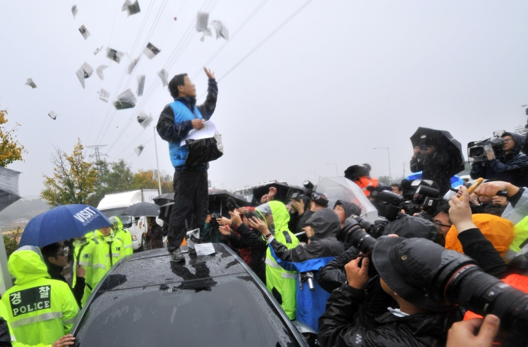 <p>Park Sang-Hak (C), an activist and former defector from North Korea, scatters anti-Pyongyang leaflets as police block his planned rally near the tense border on a roadway in Paju, north of Seoul, on October 22, 2012.</p>
