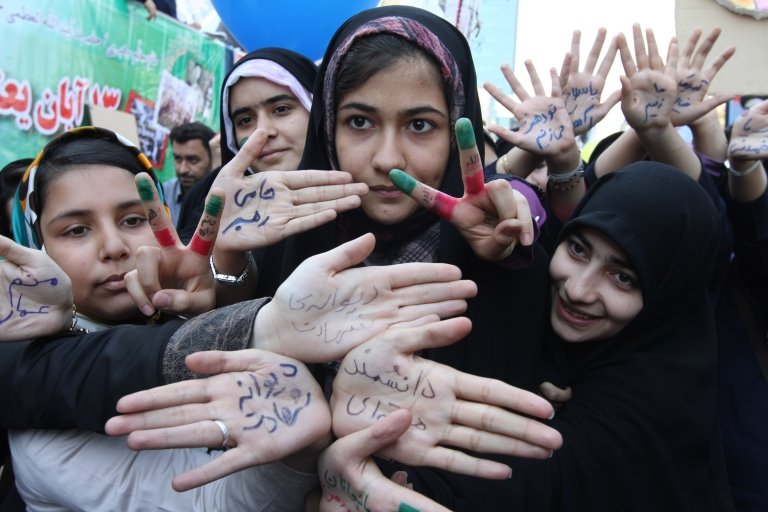 <p>Iranian students show their palms which read in Persian,