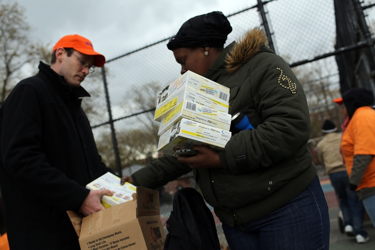 <p>A woman recieves donated water and ready-to-eat meals at the Red Hook Houses project in Brooklyn where there is currently limited water and electricity due to Hurricane Sandy on November 2, 2012 in the Brooklyn borough of New York City.</p>