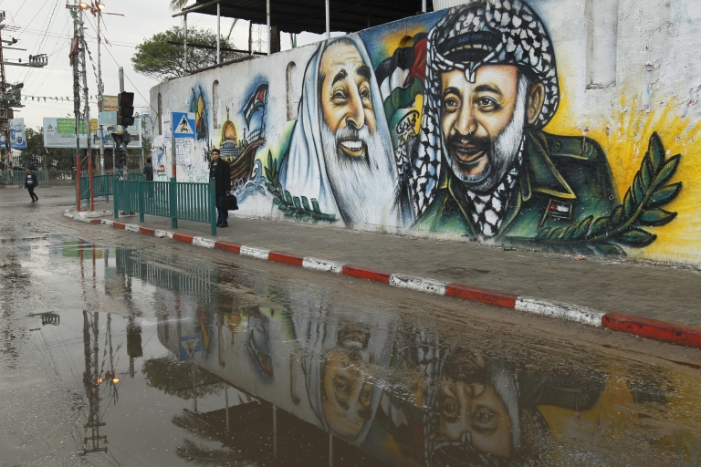 <p>A Palestinian youth stands along a side walk with a mural behind him depicting the late Palestinian leader Yasser Arafat (R) and the late Hamas spiritual leader Sheikh Ahmed Yassin in Gaza City on November 11, 2012, as Palestinians commemorate the eighth anniversary of Arafat's death.</p>