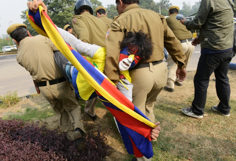 <p>A Tibetan activist shouts pro Tibetan slogans as he waves the Tibetan flag while being arrested by Indian police moments after he and some other dozen activists tried to rush thegate of the Chinese embassy in New Delhi on November 12, 2012.</p>