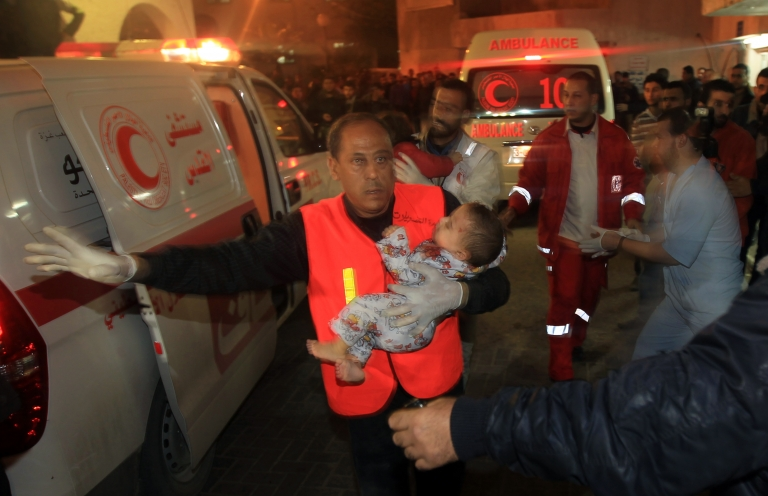 <p>Palestinian medics carry a wounded baby into the al-shifa hospital in Gaza City following an Israeli air strike on November 14, 2012.</p>