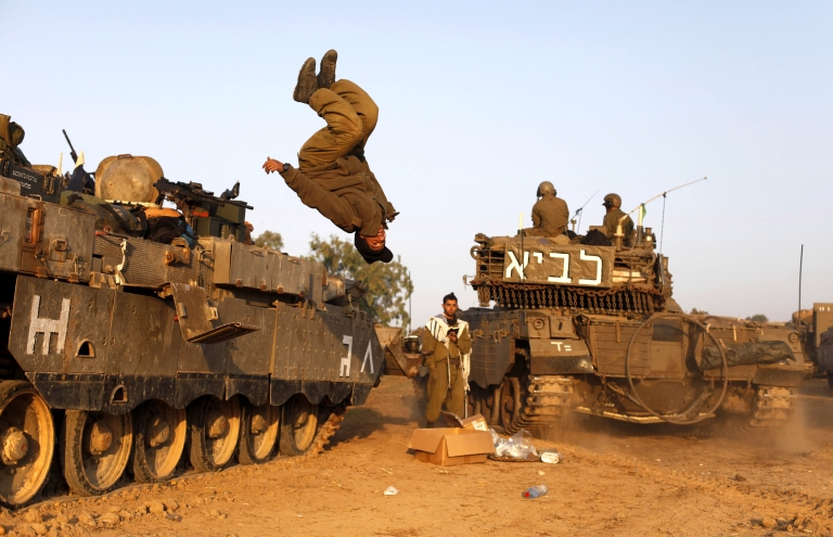 <p>An Israeli soldier jumps from a tank in a deployment area as the conflict between Palestine and Gaza enters its seventh day on November 20, 2012 on Israel's border with the Gaza Strip.</p>