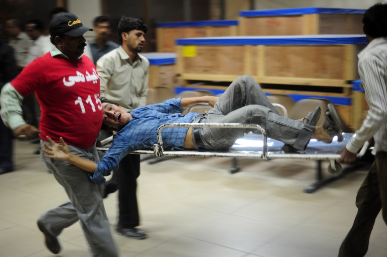 <p>Pakistani volunteers carry an injured blast victim into a hospital in Karachi on November 21, 2012. Militants hit Pakistani security forces on the eve of a major international summit, killing 10 people in regional flashpoints on Wednesday as delegates arrived in the capital Islamabad.</p>