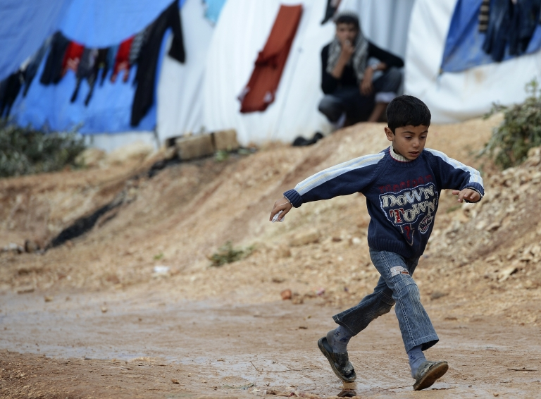 <p>A Syrian boy jumps over a pot hole on a refugee camp in Qah, near the northwestern Syria city of Idlib on November 24, 2012.</p>