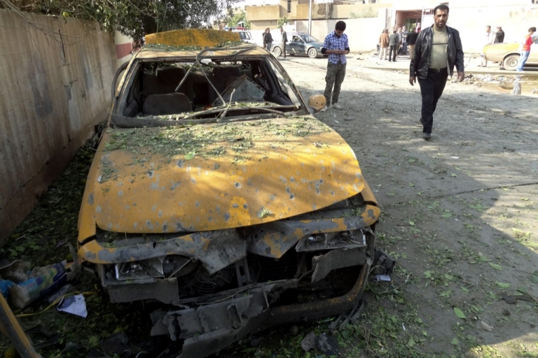 <p>A man walks past a destroyed car following three car bomb attacks in the northern Iraqi city of Kirkuk on Nov. 27, 2012. The attacks came a day after top security officials from the federal government and Iraq's autonomous Kurdistan region reached an agreement aimed at easing high tensions in disputed areas of northern Iraq, which the country's parliament speaker has warned could lead to civil war.</p>