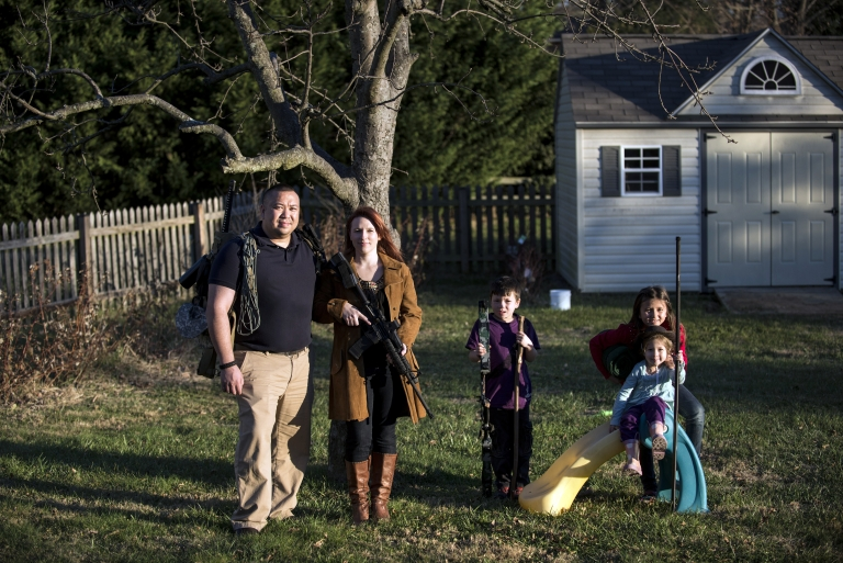 <p>Jay Blevins and his wife Holly Blevins and their children Samuel Benjamin Blevins, 7, Elliana Grace Blevins, 9, and Evangeline Joy Blevins, 4, pose beneath one of their apple trees with survival gear including a buyout bag, an AR-15 rifle and a hunting bow December 5, 2012 in Berryville, Virginia. The family has been preparing, along with a group, for a possible doomsday scenario.</p>
