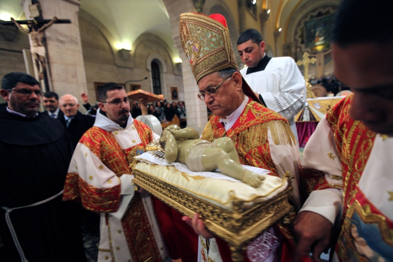 <p>Foud Twal, the Latin Patriarch of the Holy Land, holds the Baby Jesus in Saint Catherine's Church at the end of the Christmas Midnight Mass and walks in procession to the 'Grotto', where Christians believe the Virgin Mary gave birth to Jesus Christ, in the adjacent Church of the Nativity on December 25, 2012 in Bethlehem, West Bank. Thousands of pilgrims made their way to the Church of the Nativity this week to worship at the sacred site believed to be the birthplace of Jesus.</p>