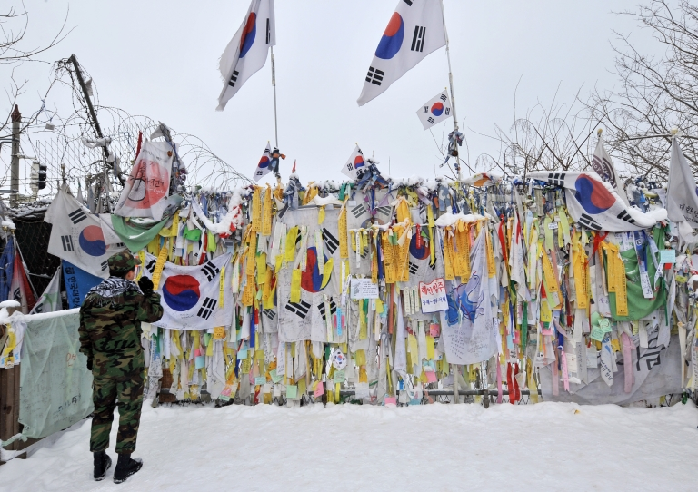 <p>A South Korean soldier looks at 'reunification ribbons' displayed on a military barbed wire fence at Imjingak peace park in Paju near the Demilitarized Zone (DMZ) dividing the two Koreas on January 1, 2013.</p>