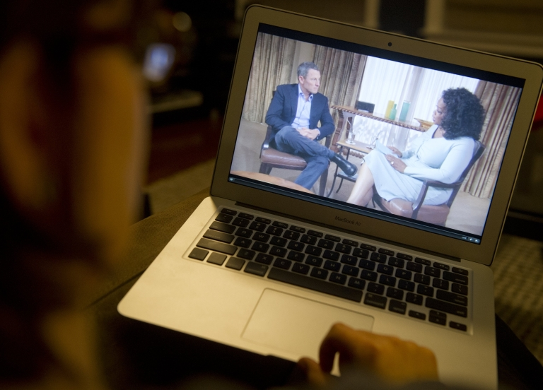 <p>A woman watches on her computer as Oprah Winfrey interviews cyclist Lance Armstrong about doping while competing professionally in the sport, as seen from Washington, DC, on January 17, 2013.</p>