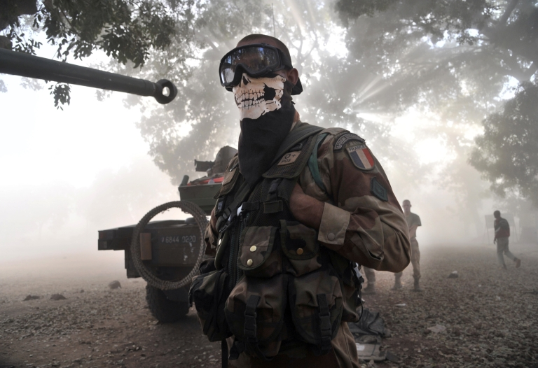 <p>A French soldier wearing a skeleton mask stands next to a tank in a street in Niono, on January 20, 2013.</p>