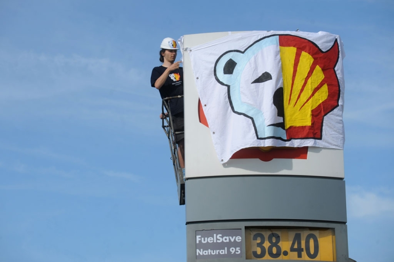<p>A Greenpeace activist covers the logo of the Shell oil company to protest on May 10, 2012 against the heading of the an icebreaker for Shell's Arctic oil drilling project in the north of Alaska.</p>