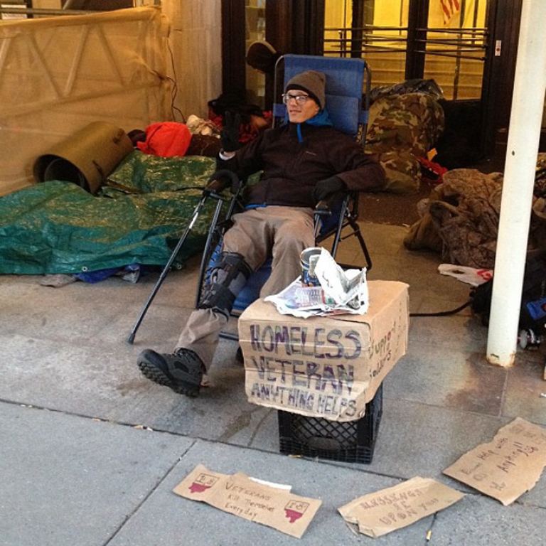 <p>Brett Glidewell sits in a folding chair at the entrance to the VA.</p>