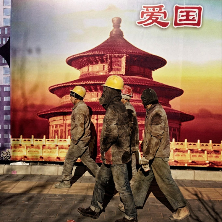<p>Migrant workers who do construction in Beijing walk by a banner showing the Temple of Heaven, a landmark in Beijing. Beijing, a sprawling metropolis, has a growing so-called