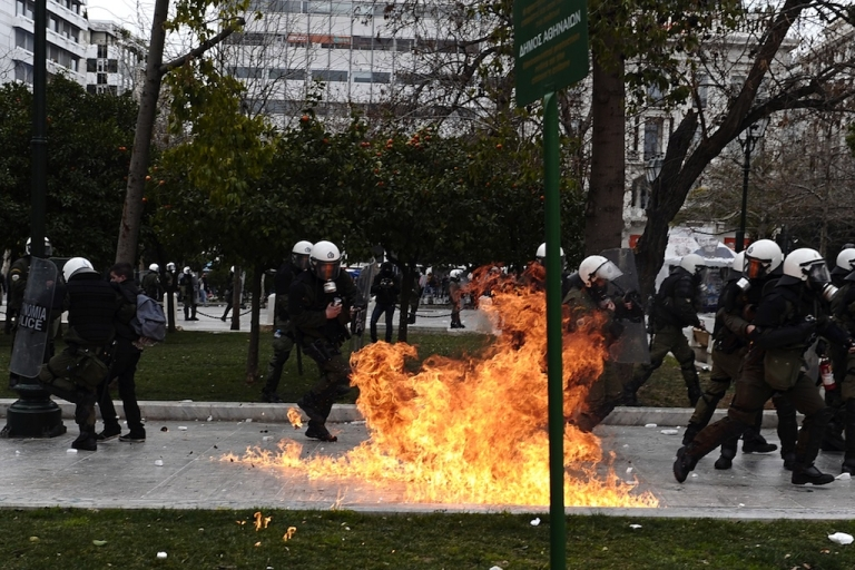 <p>Riot police dodge a firebomb in Athens on Feb. 10.</p>
