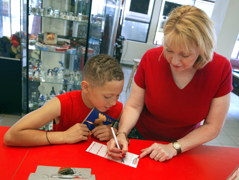 <p>Debbie Nash fills out her lottery ticket at a Citgo gas station.</p>