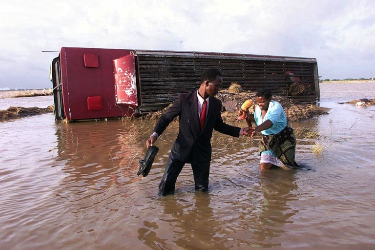 <p>A Mozambican man helps his wife cross the flooded highway to Xai-Xai from Maputo, Feb. 22, 2000. At least 700 people died, and a million were displaced, after the tropical storm 12 years ago that caused the worst floods in Mozambique's history. On Jan. 19, 2012, emergency officials in Mozambique said five people had died after Tropical Storm Dando hit the coast, causing flooding in Maputo and Gaza province.</p>