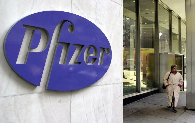 <p>A woman leaves Pfizer's New York headquarters.</p>