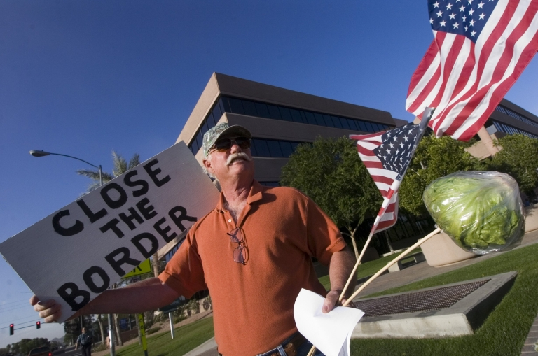 <p>Ross Withers of Camp Verde, Arizona, a member of the The Minuteman Civil Defense Corps demonstrating in front of Senator John McCain's state offices on April 14, 2006 in Phoenix, Arizona.</p>
