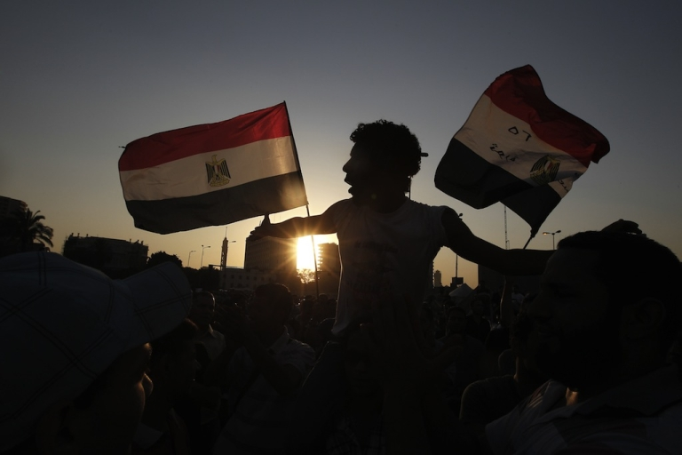 <p>Egyptian protesters wave their national flags in Cairo's Tahrir Square. Over the past year there has been little movement on human rights issues such as religious tolerance and women's rights.</p>