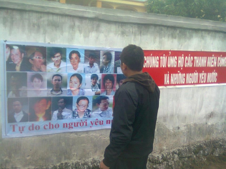 <p>A man looks at a banner representing the 14 activists convicted on January 9th in Vinh City, Vietnam. Source: thanhnienconggiao.blogspot.com</p>