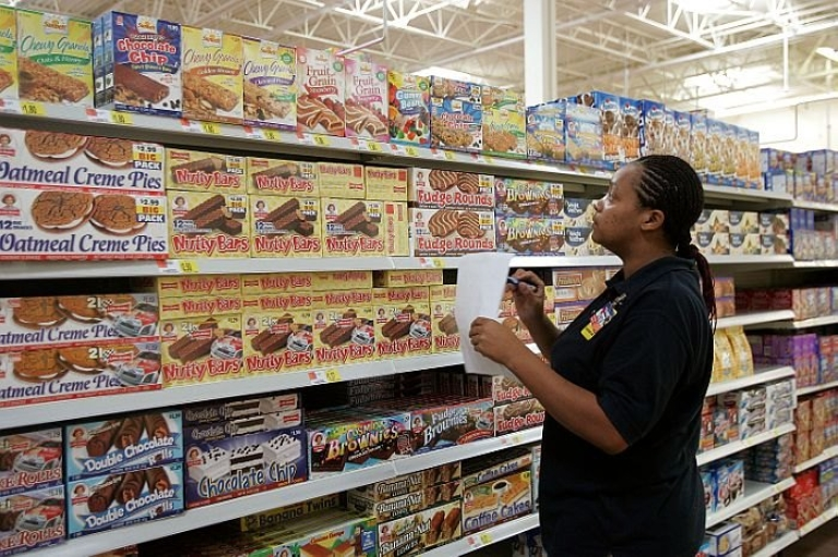 <p>An employee in a food aisle of Wal-Mart's Chicago store.</p>